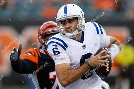 Chad Kelly, Jordan Willis. Indianapolis Colts quarterback Chad Kelly (6) runs the ball under pressure from Cincinnati Bengals defensive end Jordan Willis (75) during the first half of an NFL preseason football game, in Cincinnati