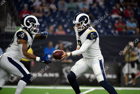 Los Angeles Rams quarterback Brandon Allen (8) hands the ball off to running back John Kelly during the first half of a preseason NFL football game against the Houston Texans, in Houston