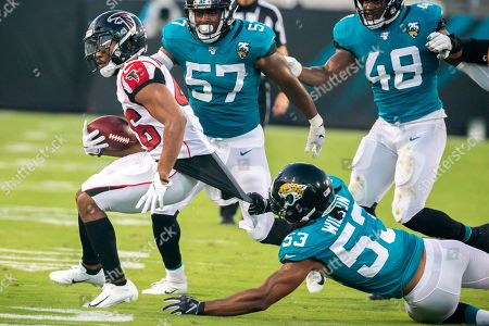 Atlanta Falcons running back Tony Brooks-James (46) has his jersey pulled by Jacksonville Jaguars inside linebacker Ramik Wilson (53) during the first half of an NFL preseason football game, in Jacksonville, Fla