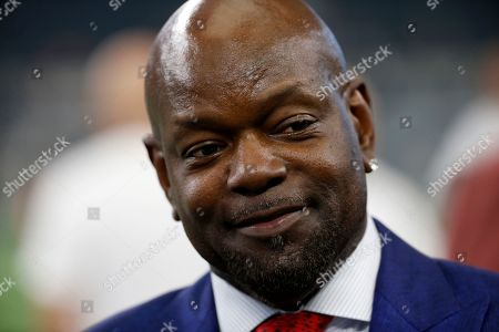 Former Dallas Cowboys player Emmitt Smith stands on the field during warmups before a preseason NFL football game against the Tampa Bay Buccaneers in Arlington, Texas
