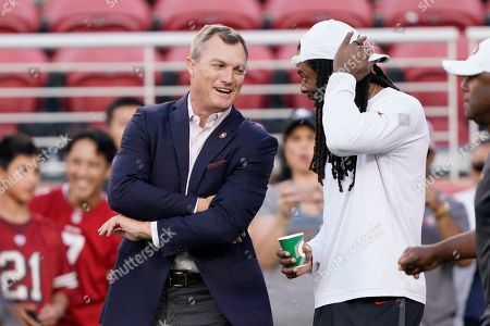 San Francisco 49ers general manager John Lynch, left, talks with cornerback Richard Sherman before an NFL preseason football game against the Los Angeles Chargers in Santa Clara, Calif