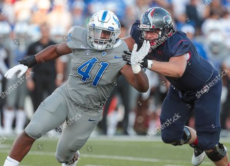 Stock Photo of Buffalo Bulls defensive end Taylor Riggins (41) battles his way past Robert Morris Colonials offensive lineman Trevor Hicks (61) during the first half of play in the NCAA Football game between the Robert Morris Colonials and Buffalo Bulls at UB Stadium in Amherst, N.Y. (Nicholas T