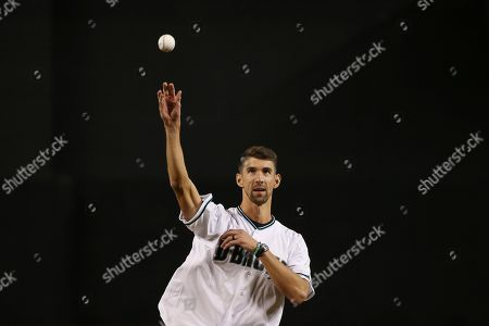 U.S. Olympic gold medal swimmer Michael Phelps throws out the first pitch prior to a baseball game between the Arizona Diamondbacks and the Los Angeles Dodgers, in Phoenix