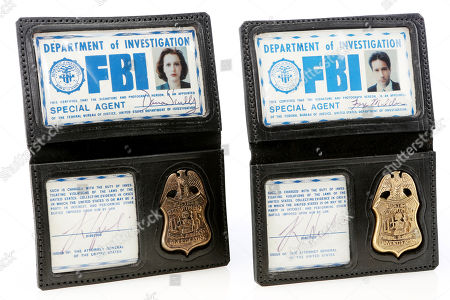 Stock Picture of Fox Mulder's (David Duchovny) and Dana Scully's (Gillian Anderson) FBI badges from the sci-fi mystery series The X-Files. Estimate: £10000 - £12000.