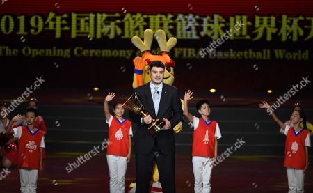 Stock Image of Former NBA player from China, Yao Ming, holds a trophy during the opening ceremony of the FIBA 2019 Basketball World Cup in Beijing on August 30, 2019.