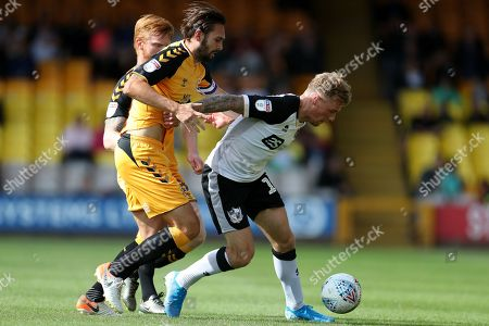 Tom Conlon of Port Vale competes with Greg Taylor of Cambridge United
