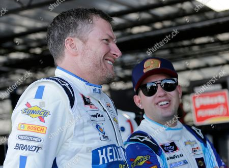 Dale Earnhardt Jr., left, talks with fellow driver Noah Gragson in the garage before practice for a NASCAR auto race, in Darlington, S.C. Earnhardt is scheduled to run in the Xfinity race on Saturday