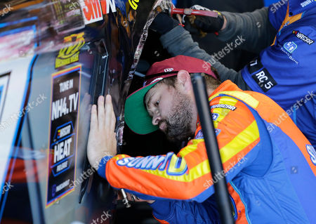 Ricky Stenhouse Jr. helps repair his car after scraping the wall during practice for a NASCAR auto race, in Darlington, S.C
