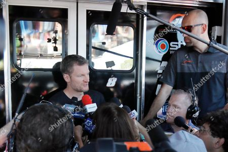 Dale Earnhardt Jr talks with the media in the garage area before practice for a NASCAR auto race, in Darlington, S.C. Earnhardt is scheduled to run in the Xfinity race on Saturday