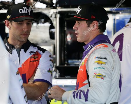 Jimmie Johnson, right, talks with a crew member in the garage after practice for a NASCAR auto race, in Darlington, S.C