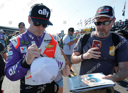 Jimmie Johnson gives an autograph after practice for a NASCAR auto race, in Darlington, S.C