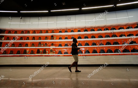 Former Texas football player Brian Orakpo walks past some of the hundreds of trophies on display at the Frank Denius Family University of Texas Athletics Hall of Fame, in Austin, Texas. Displays honor all 55 of Texas' National Championship teams, 599 conference team titles, hundreds of individual national champions, 171 Olympians at 21 Olympiads, academic All-Americans and other scholastic honorees, as well as the traditions and tales that encompass the history of Longhorns