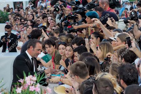 Jean Dujardin poses with fans