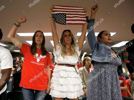 Opponents of a measure to toughen rules for vaccination exemptions, Heidi Munoz Gleisner, left, Tara Thornton, center, and Denise Aguilar, right, stand in protest after the bill was approved by the Assembly Appropriations Committee in Sacramento, Calif., . If approved by the Legislature and signed by Gov. Gavin Newsom, SB276 by state Sen. Richard Pan, D-Sacramento, would give state public health officials oversight of doctors who give more than five medical exemptions annually and schools with vaccination rates less than 95