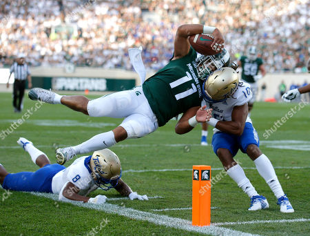 Michigan State running back Connor Heyward (11) goes over Tulsa's Brandon Johnson, left, and collides with Manny Bunch (10) as he scores on a pass reception during the first quarter of an NCAA college football game, in East Lansing, Mich
