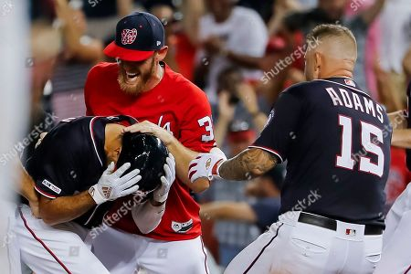 Stock Image of Washington Nationals third baseman Anthony Rendon (L) is mobbed by teammates Stephen Strasburg (C) and Matt Adams (R) after Rendon hit a game-winning two-RBI single against the Miami Marlins in the ninth inning of the MLB baseball game between the Washington Nationals and the Miami Marlins at Nationals Park in Washington, DC, USA, 30 August 2019.
