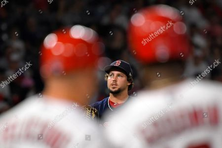 Boston Red Sox relief pitcher Josh Taylor, center stand on the mound after loading the bases as Los Angeles Angels' Brian Goodwin, right, stands next to first base coach Jesus Feliciano, left, after walking during the fifth inning of a baseball game, in Anaheim, Calif