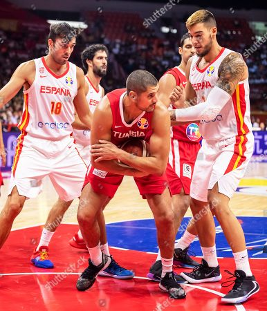 Mohamed Hadidane (C) of Tunisia in action against Spanish players Pierre Oriola (L) and Willy Hernangomez Geuer (R) during the FIBA Basketball World Cup 2019 group C match between Spain and Tunisia in Guangzhou, China, 31 August 2019.