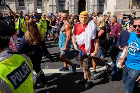 Right wing Tommy Robinson supporters are escorted through the crowds. Crowds on Whitehall protesting against the proroguing of Parliament.