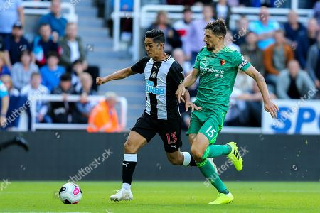 Yoshinori Muto (#13) of Newcastle United heads towards goal pursued by Craig Cathcart (#15) of Watford during the Premier League match between Newcastle United and Watford at St. James's Park, Newcastle