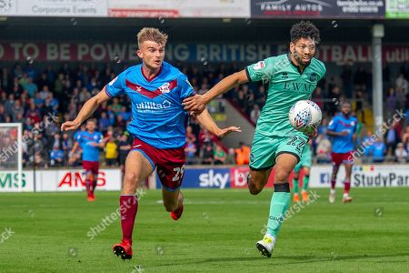 George Miller of Scunthorpe United & Nat Knight-Percival of Carlisle United chase down the ball during the EFL Sky Bet League 2 match between Scunthorpe United and Carlisle United at Sands Venue Stadium, Scunthorpe