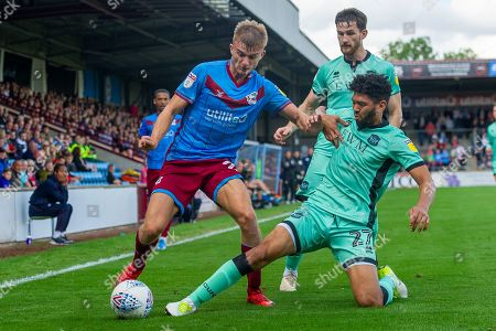 George Miller of Scunthorpe United is tackled by Nat Knight-Percival of Carlisle United during the EFL Sky Bet League 2 match between Scunthorpe United and Carlisle United at Sands Venue Stadium, Scunthorpe