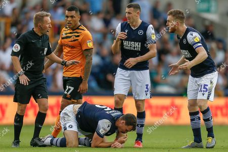 Stock Photo of Hull City forward Josh Magennis (27) eyes the Referee Oliver Langford, as Millwall defender Murray Wallace (3) and Millwall defender Alex Pearce (15) demand a card is given after a foul on Millwall defender Jake Cooper (5) during the EFL Sky Bet Championship match between Millwall and Hull City at The Den, London
