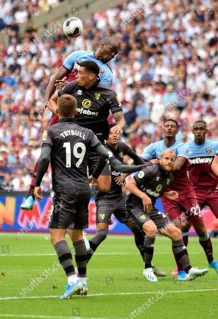 West Ham United's Angelo Ogbonna, top, challenges for the ball during the English Premier League soccer match between West Ham United and Norwich City at London Stadium in London