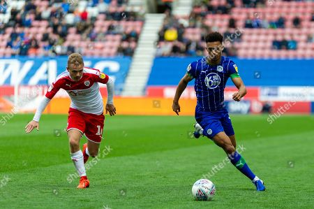 Wigan Antonee robinson runs from Barnsley Luke Thomas during the EFL Sky Bet Championship match between Wigan Athletic and Barnsley at the DW Stadium, Wigan