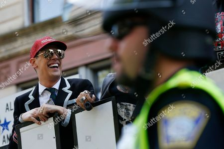 """Milo Yiannopoulos rides on a float during the Straight Pride Parade in Boston, . Several dozen marchers and about as many counter-demonstrators have gathered in Boston for a """"straight pride"""" parade. The organizers say they believe straight people are an oppressed majority"""