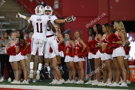 Massachusetts Minutemen wide receiver Zak Simon (11) and Massachusetts Minutemen wide receiver Cam Roberson (23) celebrate after Roberson scored a touchdown while the Rutgers Scarlet Knights cheerleaders look on during an NCAA college football game, in Piscataway, N.J. Rutgers won 48-21