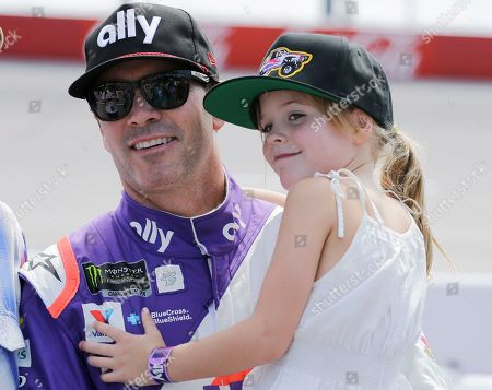 Jimmie Johnson holds his daughter Lydia on pit road before qualifying for the NASCAR Cup series auto race, at Darlington Raceway in Darlington, S.C