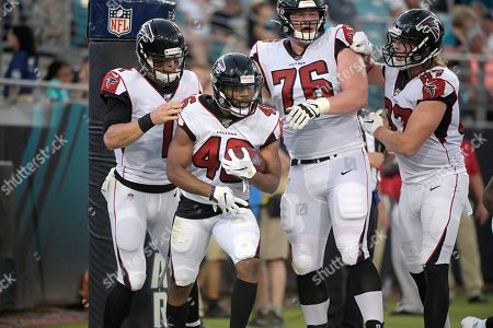 Atlanta Falcons running back Tony Brooks-James (46) is congratulated by quarterback Danny Etling (1), offensive tackle Kaleb McGary (76) and tight end Jaeden Graham (87) after rushing for a touchdown during the first half of a preseason NFL football game against the Jacksonville Jaguars, in Jacksonville, Fla
