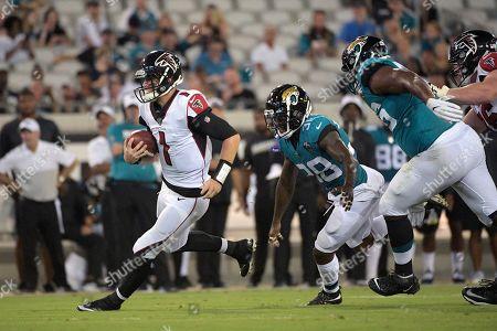 Stock Photo of Atlanta Falcons quarterback Danny Etling (1) scrambles for yardage past Jacksonville Jaguars defensive back C.J. Reavis (38) and defensive end Datone Jones (96) during the first half of a preseason NFL football game, in Jacksonville, Fla