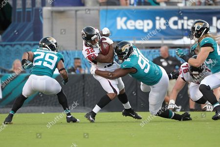 Stock Picture of Atlanta Falcons running back Qadree Ollison (32) is tackled by Jacksonville Jaguars safety Josh Robinson (29) and defensive end Datone Jones (96) after rushing for yardage during the first half of a preseason NFL football game, in Jacksonville, Fla