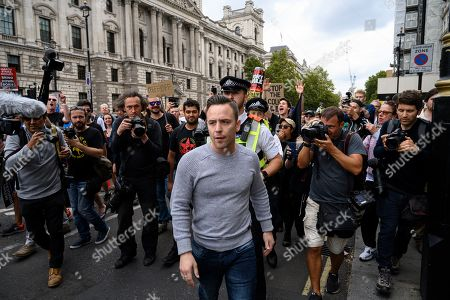 Far-right activist Daniel Thomas, an associate of Tommy Robinson, is led away from anti-Brexit protestors for his own safety.