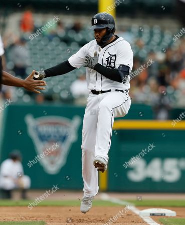Detroit Tigers designated hitter Ronny Rodriguez greets third base coach Dave Clark after a two-run home run during the third inning of a baseball game against the Minnesota Twins, in Detroit