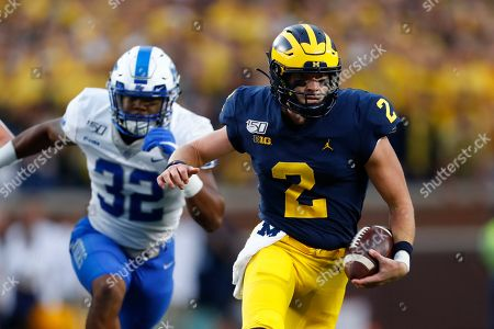 Michigan quarterback Shea Patterson (2) runs past Middle Tennessee linebacker Chris Melton (32) in the first half of an NCAA college football game in Ann Arbor, Mich