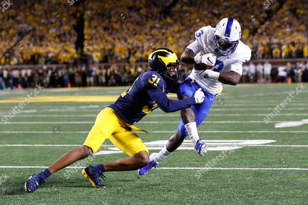 Michigan defensive back Vincent Gray (31) tackles Middle Tennessee wide receiver Tyrese Johnson (13) during the first half of an NCAA college football game in Ann Arbor, Mich