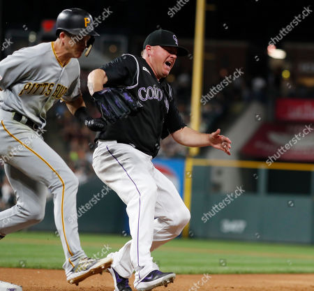 R m. Colorado Rockies relief pitcher Jake McGee, right, reacts after he missed the throw from first baseman Daniel Murphy to try and put out Pittsburgh Pirates' Kevin Newman at first base in the seventh inning of a baseball game, in Denver