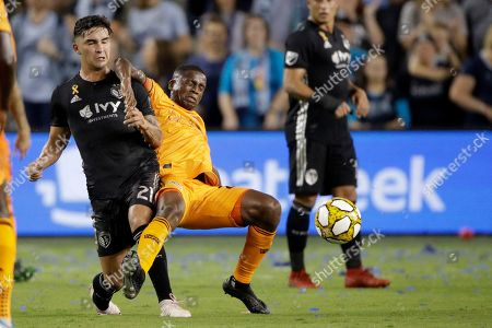 Sporting Kansas City midfielder Felipe Gutierrez (21) and Houston Dynamo midfielder Oscar Garcia collide while chasing the ball during the first half of an MLS soccer match, in Kansas City, Kan