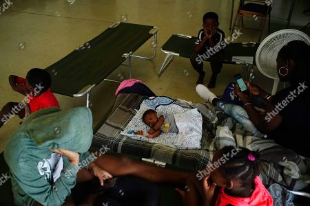 Anastacia Makey, 43, far right, looks at her phone as she and her family sits on cots with other residents inside a church that was opened up as a shelter as they wait out Hurricane Dorian in Freeport on Grand Bahama, Bahamas, . Hurricane Dorian intensified yet again Sunday as it closed in on the northern Bahamas, threatening to batter islands with Category 5-strength winds, pounding waves and torrential rain