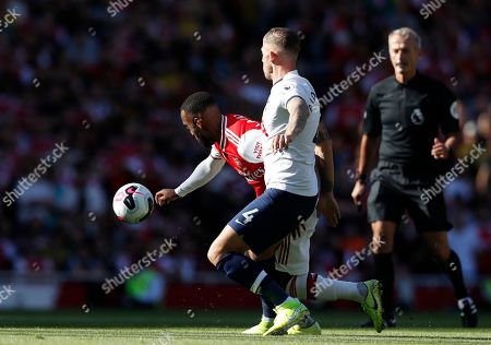Arsenal's Alexandre Lacazette, left, is challenged by Tottenham's Toby Alderweireld during their English Premier League soccer match between Arsenal and Tottenham Hotspur at the Emirates stadium in London