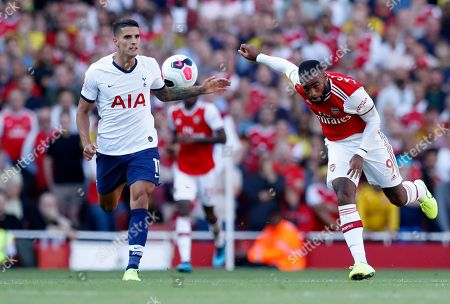 Arsenal's Alexandre Lacazette, right, fights for the ball with Tottenham's Erik Lamela during their English Premier League soccer match between Arsenal and Tottenham Hotspur at the Emirates stadium in London