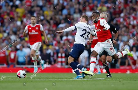 Stock Photo of Arsenal's Alexandre Lacazette pulls back Tottenham's Christian Eriksen during their English Premier League soccer match between Arsenal and Tottenham Hotspur at the Emirates stadium in London