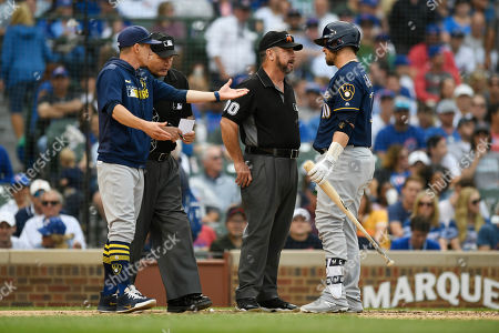 Milwaukee Brewers' Yasmani Grandal (10) and manager Craig Counsell left, argue with home plate umpire Tim Timmons, second from left, and third base umpire Rob Drake, second from right, after Grandal struck out during the seventh inning of a baseball game against the Chicago Cubs, in Chicago