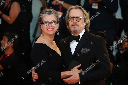 Gary Oldman, Gisele Schmidt. Actor Gary Oldman, right, and Gisele Schmidt pose for photographers upon arrival at the premiere of the film 'The Laundromat' at the 76th edition of the Venice Film Festival, Venice, Italy