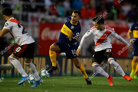 Boca Juniors' Carlos Tevez, center, dribbles the ball surrounded by River Plate's Cristian Ferreira, right, and Milton Casco during their Argentine first division soccer game in Buenos Aires, Argentina