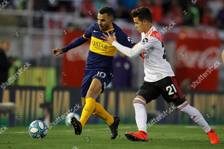 Boca Juniors' Carlos Tevez, left, and River Plate's Cristian Ferreira compete for the ball during their Argentine first division soccer game in Buenos Aires, Argentina, . The game ended in a 0-0 tie