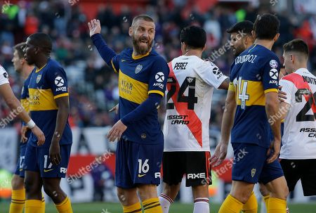 Boca Juniors' Daniele De Rossi, center, speaks to teammate Carlos Izquierdoz, right, during an Argentine first division soccer game against River Plate in Buenos Aires, Argentina, . The game ended in a 0-0 tie